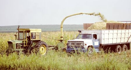 Tractor-Combine loading Truck Stock Photo