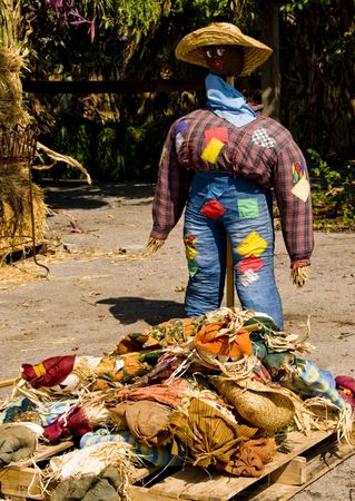 A large black straw man standing over a pile of straw dolls clothes