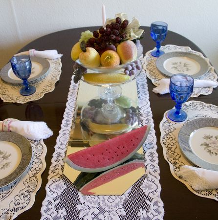 Formal table setting with watermelon and fruit bowl sitting on mirror with plates,glasses and silverware in place