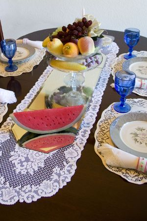 Table setting with mirrowed center piece and fruit setting on mirrow Stock Photo