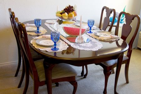 Formal Dining table with four chairs and fruit center piece sitting on a mirrow
