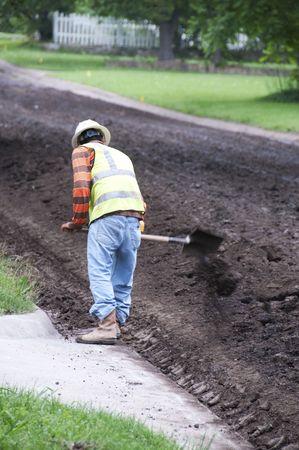 Worker shoveling dirt back into the road preparing for laying asphalt