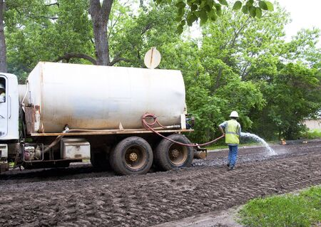 Man watering the dirt in the road prior to grading and compacting Stock Photo