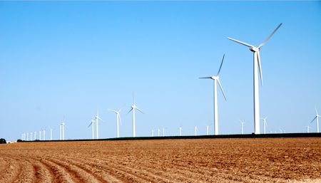 Large plowed field in west Texas with many wind turbines in th background Stock Photo
