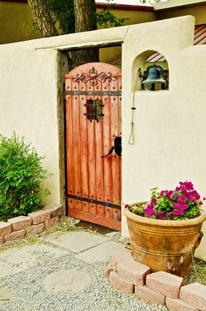 Spanish gate with flowers and shrub outside
