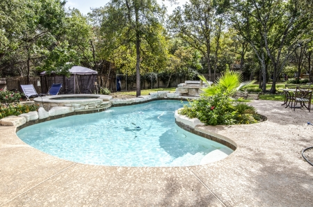 inground: Upacale backyard swimming pool that is surrounded by trees,plants, and flowers