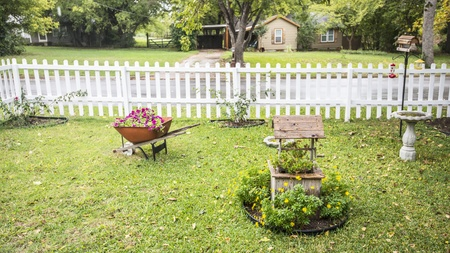 My Front Yard with flowers in wheel barrow and wishing well