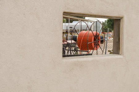 Industrial site as seen through window in wall