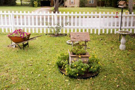 Flowers in wishing well and in wheelbarrow with birdbath  and feeder