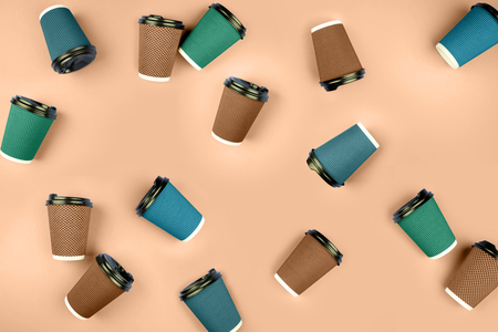 A lot of multicolored cups on a beige background. Banco de Imagens