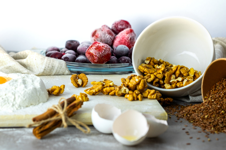 Baking ingredients on white background. Randomly scattered foods, frozen fruits, nuts, cinnamon, flax seeds, flour, eggs. Banque d'images - 117196373