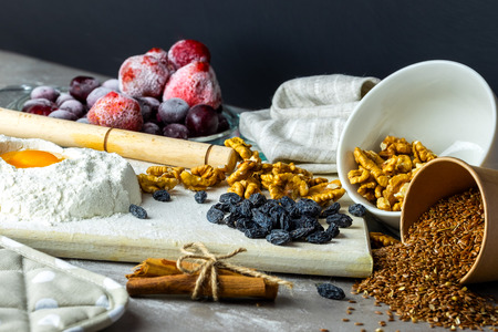 Baking ingredients on gray background. Randomly scattered foods, frozen fruits, nuts, cinnamon, flax seeds, flour, eggs. Banque d'images - 117198837