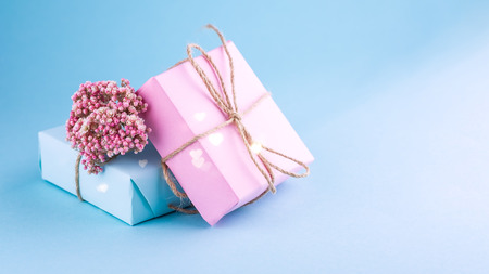Two gift boxes of pink and blue decorated with flowers on a blue background. Place for text.