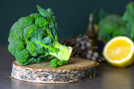 Useful foods are on the table, broccoli on a wooden stand and sliced lemon. The concept of healthy eating. Stockfoto