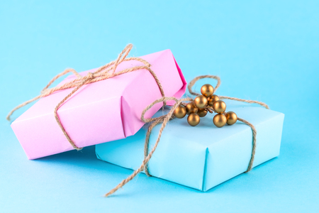 Two gift boxes of pink and blue on a blue background, minimalism photography. Place for text.