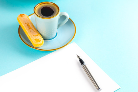 A sheet of white paper is empty on a blue background with an ink pen ,there is also a blue cup with coffee on a saucer and a plate with Savoyardi biscuits. Place for text.