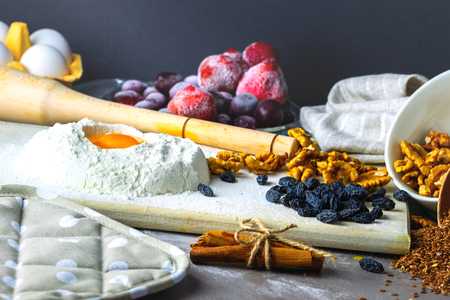 Baking ingredients on gray background. Randomly scattered foods, frozen fruits, nuts, cinnamon, flax seeds, flour, eggs. Banque d'images - 119947094