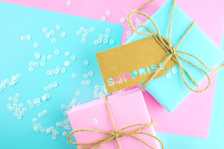 Two gift boxes of pink and blue, tied with twine, on a pink-blue background. Gift tag with the inscription surprise .