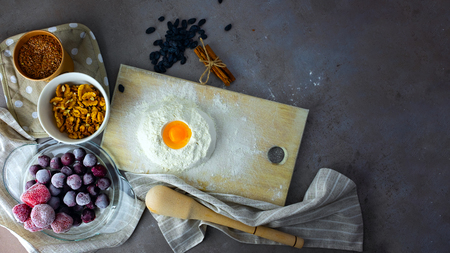 Baking ingredients on gray background. Randomly scattered foods, frozen fruits, nuts, cinnamon, flax seeds, flour, eggs. Healthy eating concept. Place for text. Banque d'images - 119947170