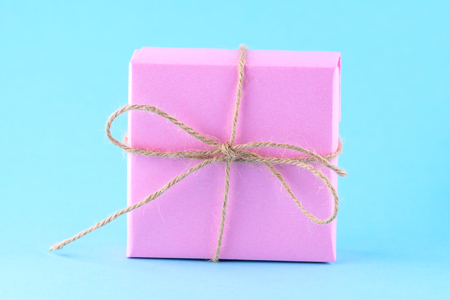 Pink gift box tied with string on a bright blue background, minimalism, parcel, place for text.
