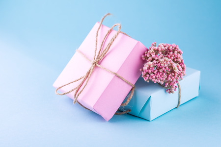 Two gift boxes of pink and blue with bows of twine decorated with small pink flowers on a blue background ,the concept of handmade.