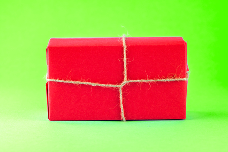 Red gift box tied with string on a bright green background, minimalism, parcel, place for text.