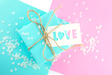 Two gift boxes of pink and blue, tied with twine, on a pink-blue background. Gift tag with the inscription love.