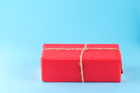 Red gift box tied with string on a bright blue background, minimalism, place for text.