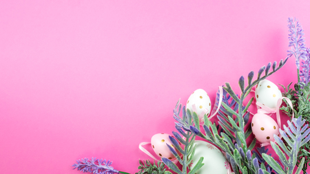 Easter background of pink color with eggs and ornamental plants. Place for text.