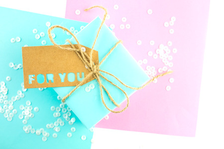 Two gift boxes of pink and blue, tied with twine, on a pink-blue background. Gift tag with the inscription for you .