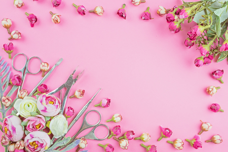 Manicure tools on a pink background decorated with flowers. Beauty concept. Place for text.