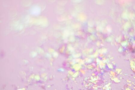 Blurred abstract background of glitter and foil hologram. Glittering dust particles. Backdrop for your design.