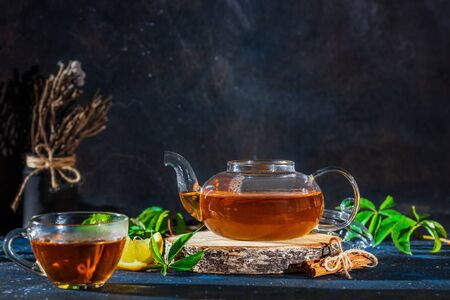 Tea cup with hot tea and tea pot. Place for text .