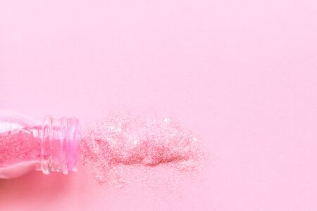 An open glass jar from which spangles of pink color spilled out on a pink background. 免版税图像