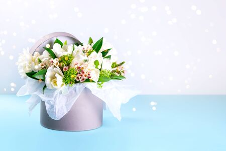 A box with white tulips and ornamental plants on a blue background. Place for text. 写真素材