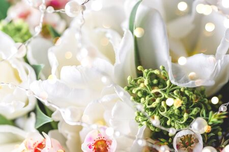 Beautiful bouquet of white tulips with green leaves and other decorative flowers close up.