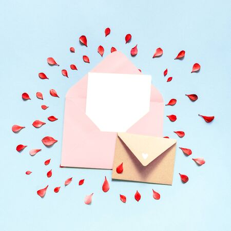 Envelope of pink color inside which is a blank white sheet of paper, the background is blue. Red leaves. Place for your design.