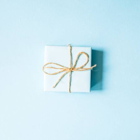 Blue gift tied with twine on a blue background, minimalism concept. Place for text. Flat lay. Stock Photo