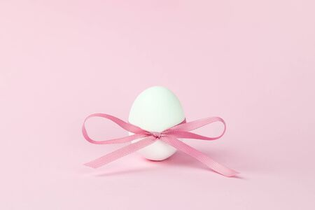 close-up Easter egg decorated with a pink bow on a pink background, festive minimalism. Holiday concept. Keto diet, a healthy food product.