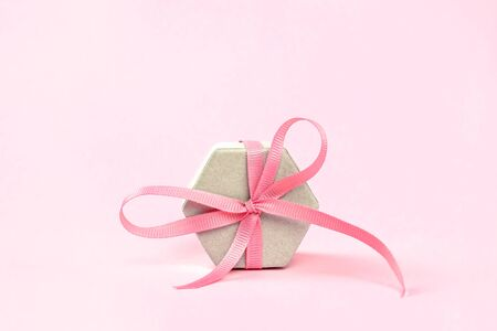 Gift box of irregular shape tied with a pink ribbon on a pink background. Festive minimalism concept. Copy space.