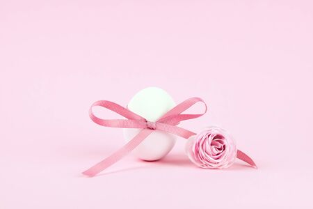 Easter egg close-up decorated with a pink bow on a pink background, festive minimalism. Reklamní fotografie