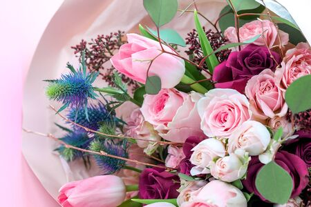 A closeup bouquet of roses and tulips decorated with leaves and twigs of other beautiful plants. Holiday concept. Flowers for Mothers Day. Copy space.