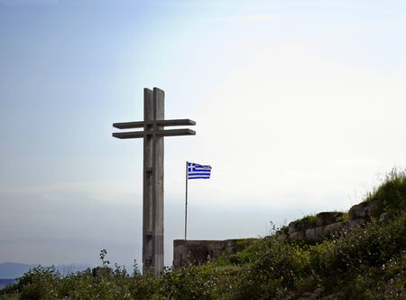orthodoxy: a big wooden cross with the greek flag