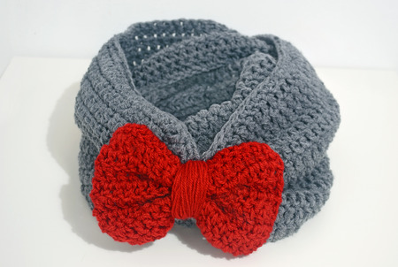 acrylic yarn: crochet infinity scarf with red bow Stock Photo