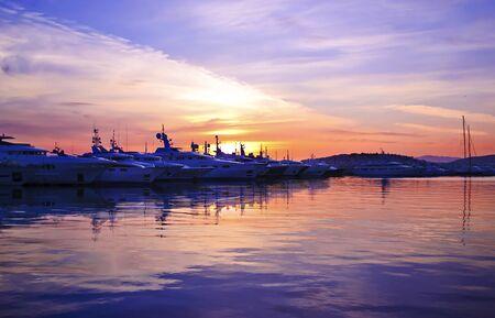 purple sunset: purple sunset behind the boats - water reflections - night boat sunset Stock Photo