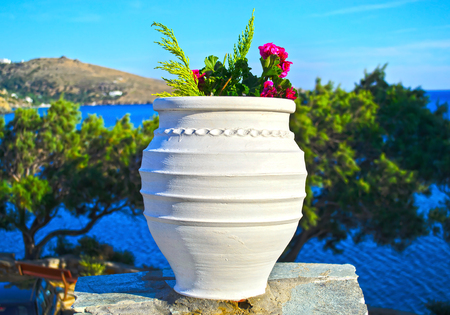cycladic: cycladic flower pot in Andors island Greece - island landscape background Stock Photo
