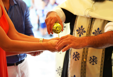 godfather: Orthodox christening -  the priest puts the baptism oil on the hand of godmother Stock Photo