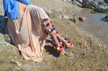 woman sandals: woman advertises traditional greek sandals gladiator on beach