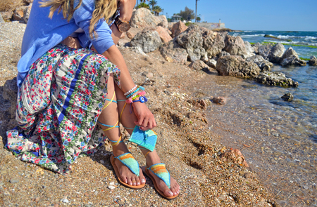 advertises: woman advertises handmade accessories on beach - greek sandals bag and jewelry Stock Photo