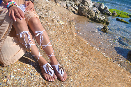 advertises: woman advertises traditional greek sandals and jewelry on beach
